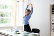 Leinwanddruck Bild - Businesswoman Stretching Her Arms At Workplace
