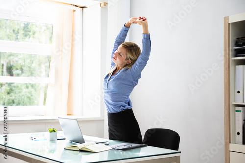 Leinwanddruck Bild Businesswoman Stretching Her Arms At Workplace