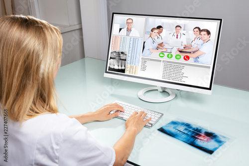 Dentist Video Conferencing With Her Colleagues On Computer - 227407668
