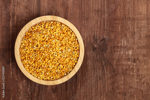 Foto Murales Healthy organic food. A top shot of pollen in a wooden bowl on a dark rustic background with copy space