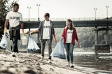 Volunteers with bags. Company of three active responsible volunteers walking near the river with garbage bags gathering trash - 227425677