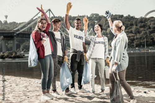 Obraz na płótnie Near the bridge. Teacher and active beaming pupils feeling joyful meeting on weekend while volunteering near the bridge