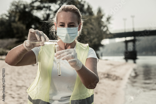 Fototapeta Near the bridge. Professional sanitary inspector wearing mask standing near the bridge with two test tubes checking purity of water