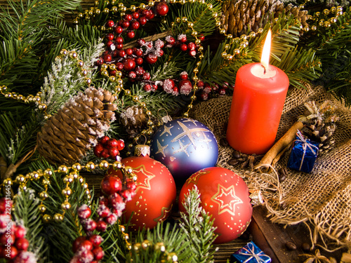 Foto Murales Christmas cozy still life with a candle, Christmas decorations pine cones