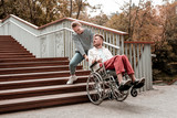 Heavy wheelchair. Upset young man turning his head and looking at the weak young woman carrying his wheelchair upstairs - 227433086