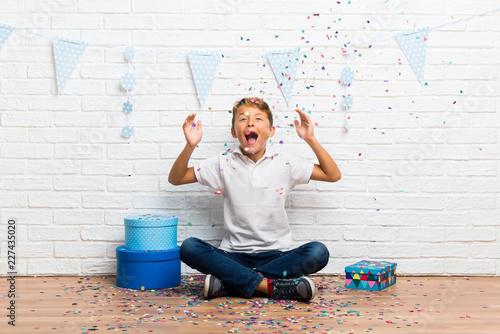 Leinwandbild Motiv boy celebrating his birthday with confetti in a party