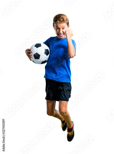 Leinwanddruck Bild A full-length shot of Boy playing soccer and jumping on isolated white background