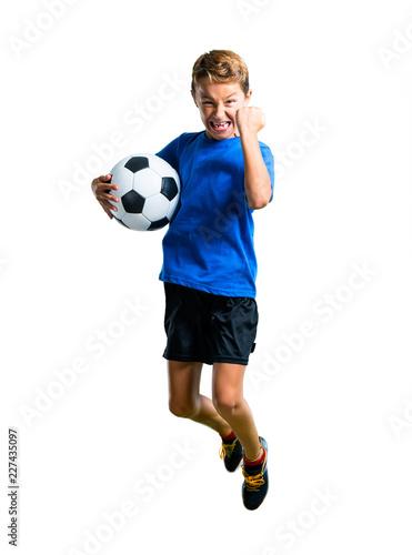 Leinwandbild Motiv A full-length shot of Boy playing soccer and jumping on isolated white background