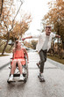 Riding and smiling. Positive active young man spending time with his pretty smiling disabled girlfriend and riding his amazing skateboard