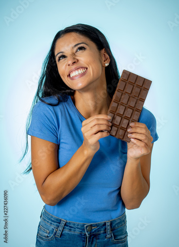 Leinwandbild Motiv Young attractive brunette feeling joy and guilt at the thought of eating chocolate