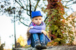 little girl in a blue hat sits and sad autumn sunny day