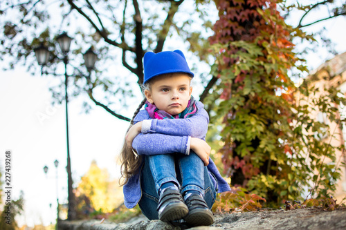 Leinwanddruck Bild little girl in a blue hat sits and sad autumn sunny day