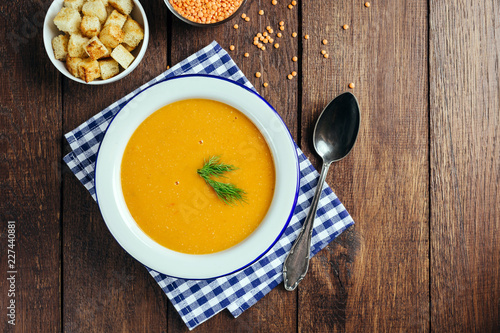 Lentil soup, white plate, blue checkered napkin, wooden background, bean, home cooking - 227440881