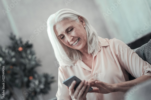 Foto Murales Newest technology. Pleasant delighted nice woman smiling and using her mobile gadget while sitting on the sofa