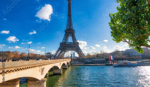 Poster PARIS, FRANCE - DECEMBER 2012: Tourists visit Eiffel Tower. The city attracts 40 million people every year