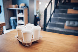 Take coffee to work for the entire office. High angle shot of a cardboard take out tray with four coffee cups with lids - 227461280