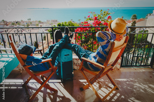 Leinwanddruck Bild father and son relax on balcony terrace with suitcase, travel concept