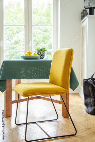 Fruit Bowl On A Wooden Table And Modern Chair With Bright Yellow Upholstery In