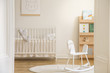 Quadro Rocking horse on rug in white kid's bedroom interior with rabbit poster above cradle. Real photo