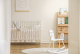 Rocking horse on rug in white kid's bedroom interior with rabbit poster above cradle. Real photo