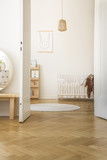 White round rug next to baby's cradle in bedroom interior with rabbit poster and pillows. Real photo