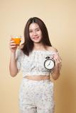 Asian woman with a clock drink orange juice. - 227485829