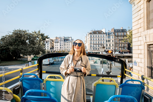 Young woman enjoying a beautiful view on the city during a bus tour in Paris, France