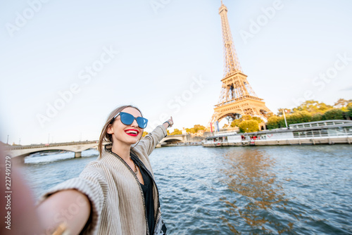 Young woman tourist making selfie photo with Eiffel tower on the background from the boat during the sunset in Paris
