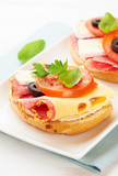 Sandwiches with salami, cream cheese, tomatoes, camembert, black olives, fresh parsley and basil served on a plate. Home made food Symbolic image Concept for a tasty and healthy meal White background  - 227504279