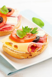 Sandwiches with salami, cream cheese, tomatoes, camembert, black olives, fresh parsley and basil served on a plate. Home made food Symbolic image Concept for a tasty and healthy meal White background  - 227504436