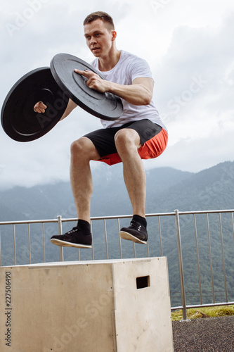 Athlete jumping with weight plates on the box on nature background. Motion shot of powerful well-built bodybuilder performing box jumps in mountain, close up. fitness concept