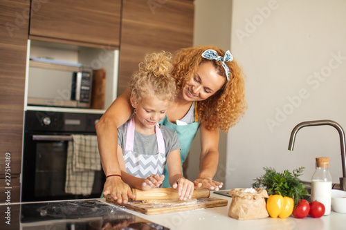 Leinwandbild Motiv Beautiful young mom and her little daughter with funny curls rolling dough for cookies with rolling pin and smiling while baking in kitchen at home