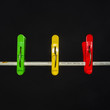 three colored clothespins on a clean black background