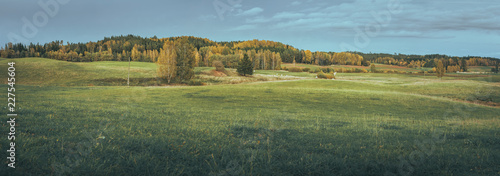 Landscape of countryside in Latvia in autumn colors. Panoramic view over farm land and foothills. Colorful forest in the background of the village. - 227545604