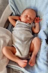 Baby boy sleeping in the bouncer