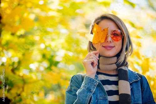 Leinwandbild Motiv Young beautiful blonde girl in blue jeans clothes have rest in the park in autumn season time.