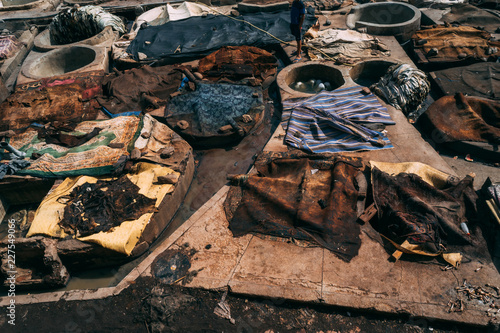 overhead view of men traditionally stacking dyed garments at a leather tannery in a moroccan residential neighborhood