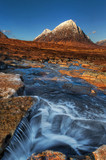 Scottish mountain scene with small river and snow