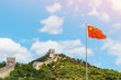 The Great Wall of China. Chinese flag against the background of the blue sky and of the Great Wall. Toned