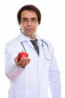 Studio shot of young Persian man doctor giving red apple