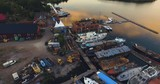 Aerial reveal of an old colorful boatyard outside the swedish east coast with beautiful sunset reflections in the water. - 227587472
