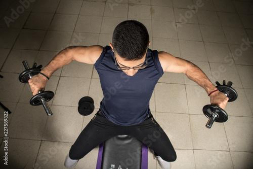 Mężczyzna ćwiczy z dumbbells, ramienia ćwiczenie