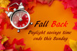 Fall back, the end of daylight savings time and turn clocks back on hour concept with a clock surrounded by dried yellow leaves with the text Fall back, daylight savings time ends this Sunday