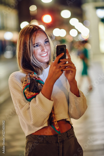 Sticker Woman taking photograph with smartphone at night in the street