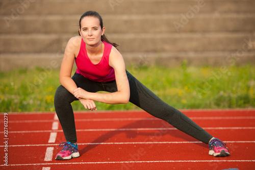 Piękna młoda kobieta robi longe krokowi na sportowym śladzie