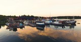 Low aerial view of old colorful boatyard outside the swedish east coast with beautiful sunset reflections in water. - 227612808