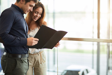 Young handsome caucasian businessman reading an advertising booklet at the car dealership while his beautiful wife embracing him, standing nearby.