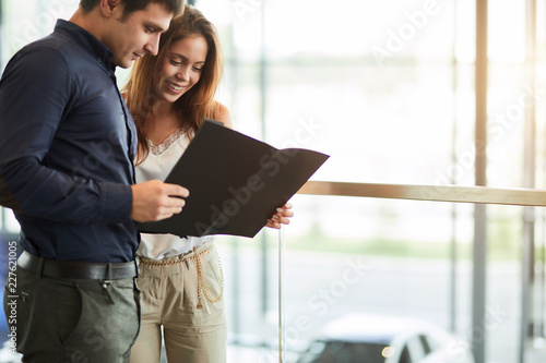 Leinwandbild Motiv Young handsome caucasian businessman reading an advertising booklet at the car dealership while his beautiful wife embracing him, standing nearby.