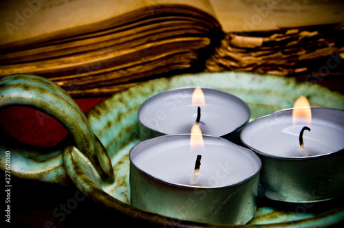 three candles with old book like esoteric, magic, spiritual, religious, occult ritual concept