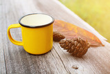 Yellow cup of coffee on wooden table with pine cone - 227632282